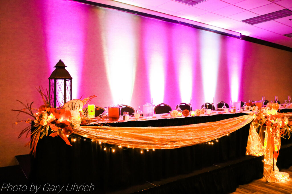 Lighting, flowers, lantern, and fall decor at the head table.
